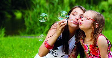Woman and young girl blowing bubbles in park