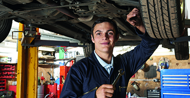 Young man fixing underside of car